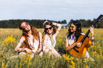 Three cute hippie girl sitting on grass outdoors, best friends having fun and laughing, playing the guitar, sunglasses, feathers in their hair, bracelets, flash tattoo, indie, Bohemia, boho style