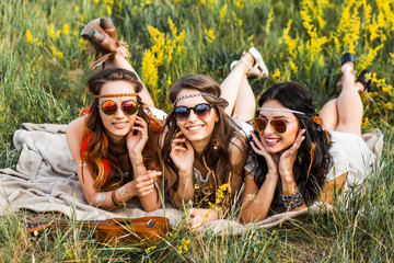 Three cute hippie girl lying on the grass among the wildflowers, best friends having fun and laughing, accessories sunglasses, feathers in their hair, bracelets, flash tattoo, indie Bohemia boho style