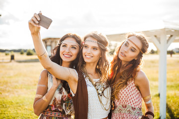 Three cute hippie girl in the setting sun, photographed themselves, the best of friends smiling and having fun, long hair, feathers in their hair, bracelets, flash tattoo, indie, Bohemia, boho style
