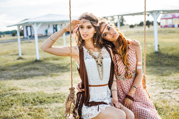 Two cute hippie girl in the setting sun, and ride on a swing, outdoors, best friends having fun and laughing, long hair, feathers in their hair, bracelets, flash tattoo, indie, Bohemia, boho style