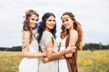Three beautiful cheerful hippie girls, best friends, the outdoors, cute smile, trendy hairstyles, feathers in her hair, white dress, tattoo flash, gold accessories, Bohemian, boho style, fashion indie