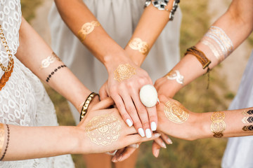 Close-up of female hands, three girls, best friends, flash tattoo, accessories, Bohemian, boho style, indie hippie, ring, bracelet, manicure, feathers