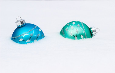 Teal blue and green Christmas ornaments buried in snow