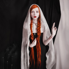 red-haired girl with red lips and pale skin and tear on cheek a woman with long red hair tied in braids with a veil on head, cuts on hand, a black gothic clothes, smoke of incense, black background