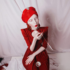 redhead smoking girl with red lips and a red turban on a white background, woman with a white skin with a ring on her finger and a mouthpiece in hand, a bright unusual appearance, albino
