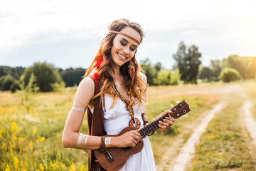 Pretty amazing free red-haired hippie girl playing a ukulele outdoors, feathers and braids in her hair, white dress, leather and gold accessories, flash tattoo, indie, Bohemia, boho style, nice smile