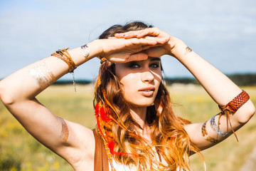 Pretty free red-haired hippie girl covers her eyes with her hands from the sun, outdoors, feathers in her hair, white dress, leather accessories, flash tattoo, indie, Bohemia, boho style, fashion