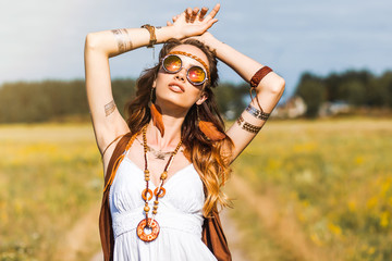 Pretty amazing free red-haired hippie girl dancing outdoors, feathers and braids in her hair, white dress, vest with fringe, accessories, sunglasses, tattoo flash, indie, Bohemian, boho style