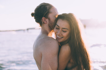 couple is giving each other hug at the beach when is sunset