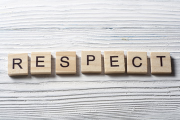 RESPECT word written on wood block ta wooden background