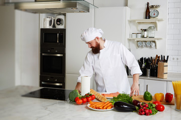 Handsome male chef in uniform prepare his kitchen for began to cook