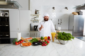 Smiling happy chef pointing with finger to you standing on big kitchen