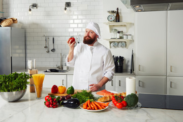 Chef holding beautiful red tomato in the hand and look to the camera
