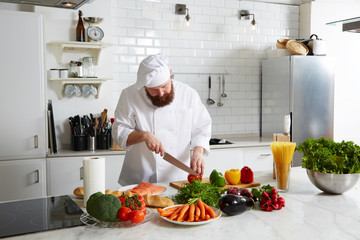 Professional cook cut vegetables in the kitchen, experienced chef making pasta on big kitchen