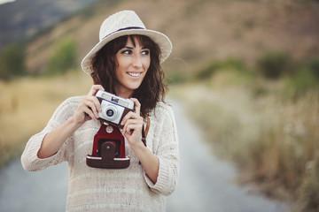 chica sonriente con cámara de fotos en el campo