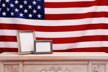 Two photo frames with USA flag on wooden mantelpiece