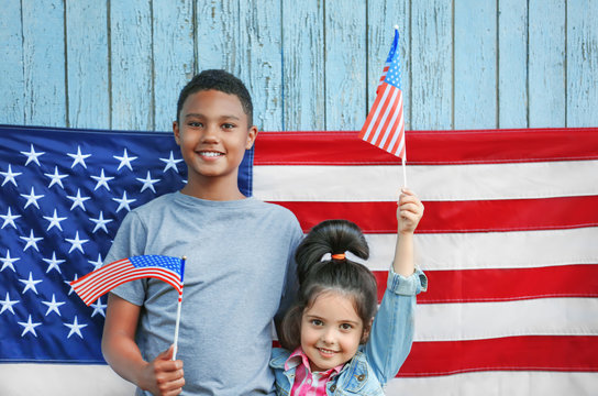 Boy and small girl with American flags on wooden background