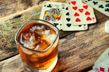 Whiskey, cigar and cards on a wooden background