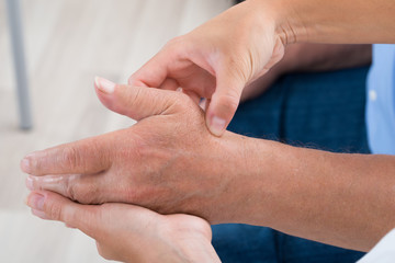 Physiotherapist Massaging Palm Of A Man