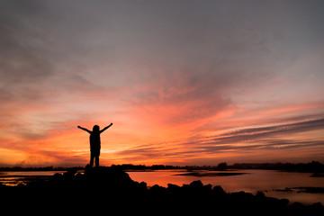 silhouette girl Happy celebrating winning success at sunset