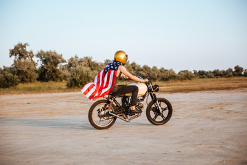Side view of man in american flag cape driving motorcycle