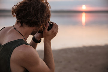 Man making photo of sunset with camera outdoors