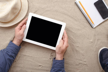 Man holding tablet with blank screen lying on the beach