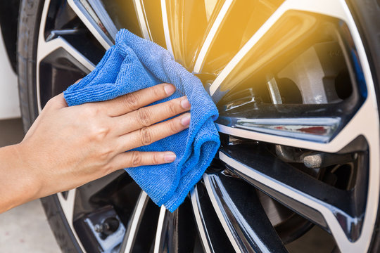 Hand with blue microfiber cloth cleaning car wheel.