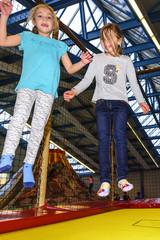 Zwei Mädchen gemeinsam auf dem Trampolin