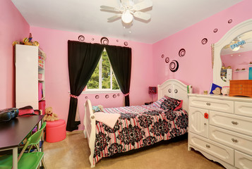 Beautiful girls room in bright pink color with carved wood bed