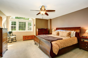 Bedroom interior with wooden furniture and carpet floor.