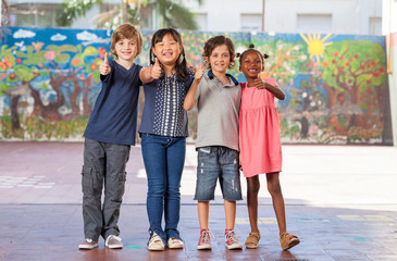 Elementary multi ethnic class children embracing happy at school