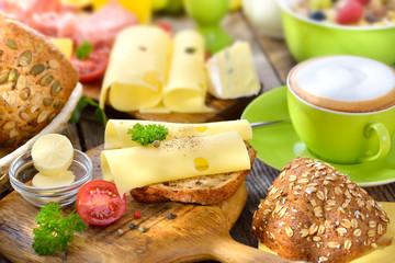 Rustikaler, bunter Frühstückstisch mit Käseröllchen und weiterer reichlicher Auswahl - Outside served colorful breakfast with a large selection of food and a cup of cappuccino