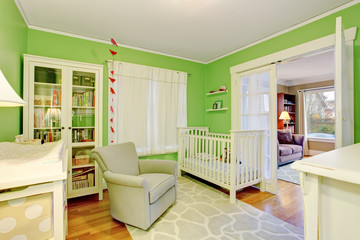 Kids room in white and green tones with beige armchair