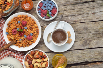 Breakfast table - berries, homemade granola, milk, dried fruits, nuts on wooden background. Copyspace background.Top view.