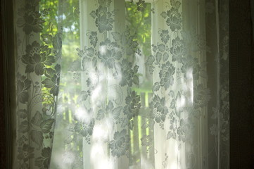 Sunlight shining through the window from the garden. Through the tulle and curtains