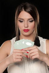 Beautiful serious woman holding playing cards in her hands