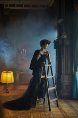 Thoughtful woman in dark evening gown stands on the step-ladder