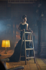 Lady dressed for a party poses on a wooden ladder
