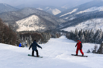 Snowboarders, descent from the mountain.