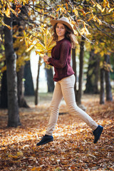 Happy smiling girl jumping /running in the forest. Young woman c