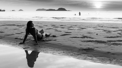 Beautiful young woman on the beach. Black and white photo.