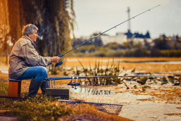 Senior man fishing on a freshwater lake sitting patiently