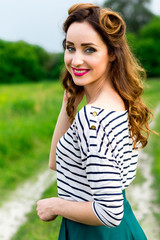 Beautiful young girl in retro style walks in the meadow
