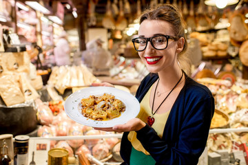 Young woman sitting near the food shop with traditional italian appetizer on the blurred food showcase background in Bologna city. Bologna is the gastronomic center of Italy