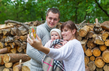 Autumn scene of Happy young family taking selfie with smartphone in forest