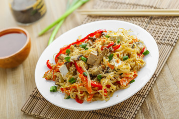 Stirred rice noodles with vegetables, tofu and shiitake mushroom. Traditional Asian food.