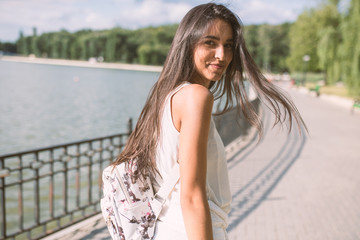 Attractive portrait of young brunette woman with beautiful smile, with a windy long hair, on park background with a lake. Looking from the back. Travel.