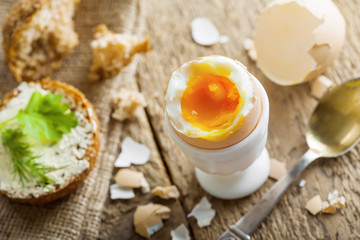 Breakfast with perfect soft boiled egg and sandwich with cheese. Traditional homemade food.