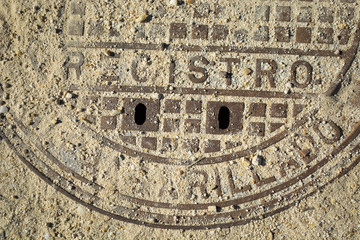 Detail of rusty manhole cover detail with words in Spanish blocked by sand and pebbles